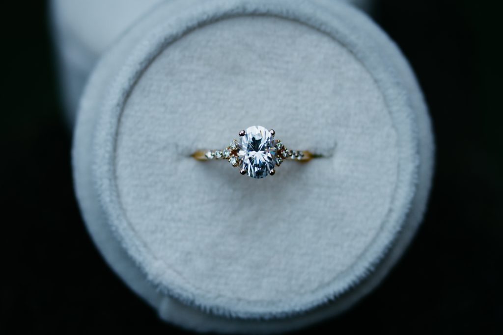 Oval moissanite engagement ring with lab diamond accent stones. Custom made in 14KT yellow gold.