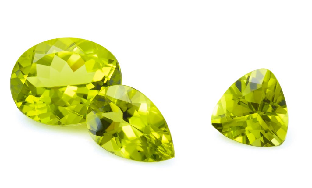 3 loose peridot gemstones. A trillion, pear, and oval shape.
