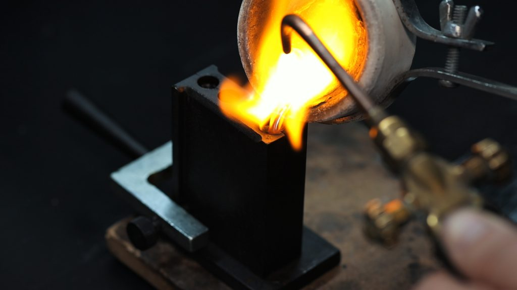 Pouring gold into an ingot mold.