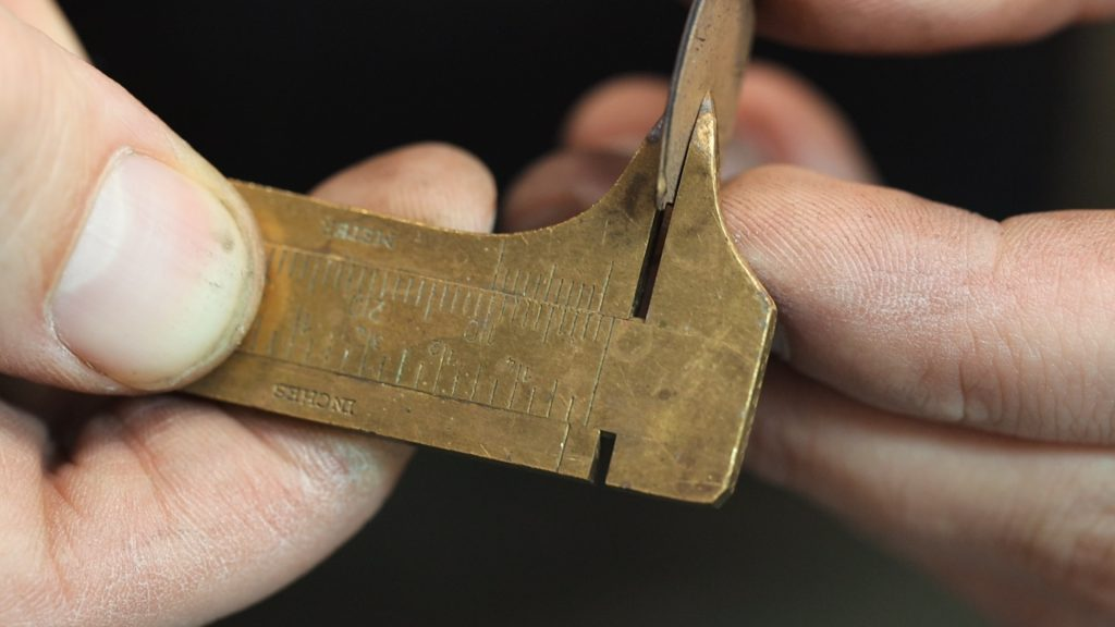 measuring the gold thickness with a millimeter gauge.